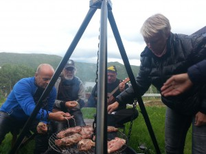 Grilling på bålpanne, en hyggelig start på turen. Anne og Per Martin ordner grillmaten mens Tore spiller opp. Tor venter forventningsfullt.