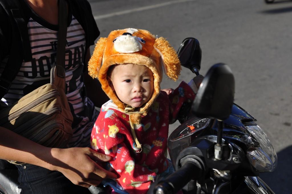 Den skal tidlig krøkes den som god thai skal bli. Denne pjokken er trafikksikret etter thaistandard – han har lue i det kalde været.