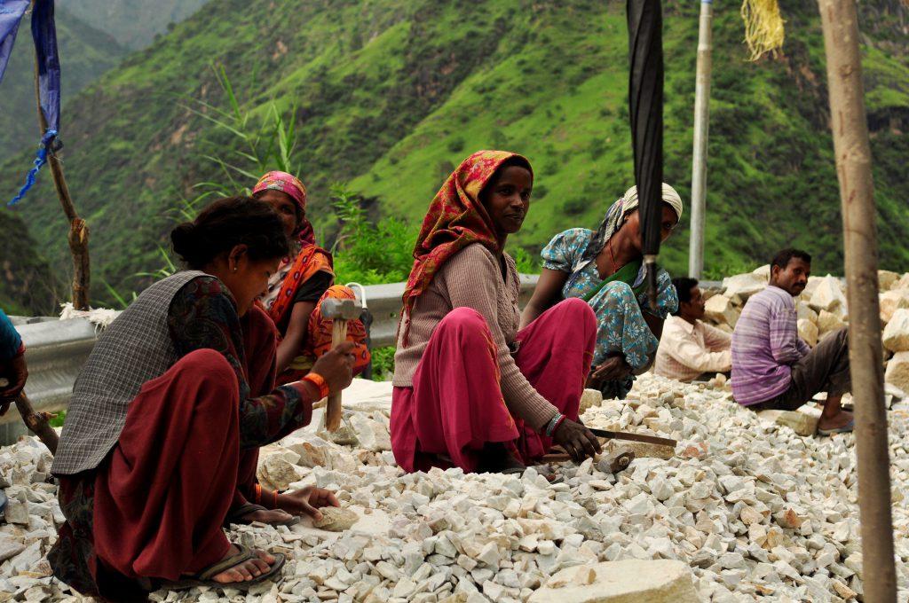 Veibygging i India er håndarbeid. Store steiner knuses med slegge og blir til grus. En spade betjenes av to indere. En liten samling mennesker har tydeligvis ansvar for hver sin lille strekning.