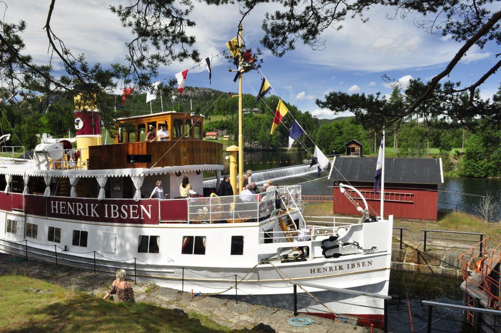 Vi møter Henrik Ibsen på vei nedover kanalen fra Dalen. Båten er fra 1907 og seilte i den svenske skjærgården frem til 1992. Da ble den satt i drift på Telemarkskanalen i forbindelse med kanalens 100-årsjubileum.